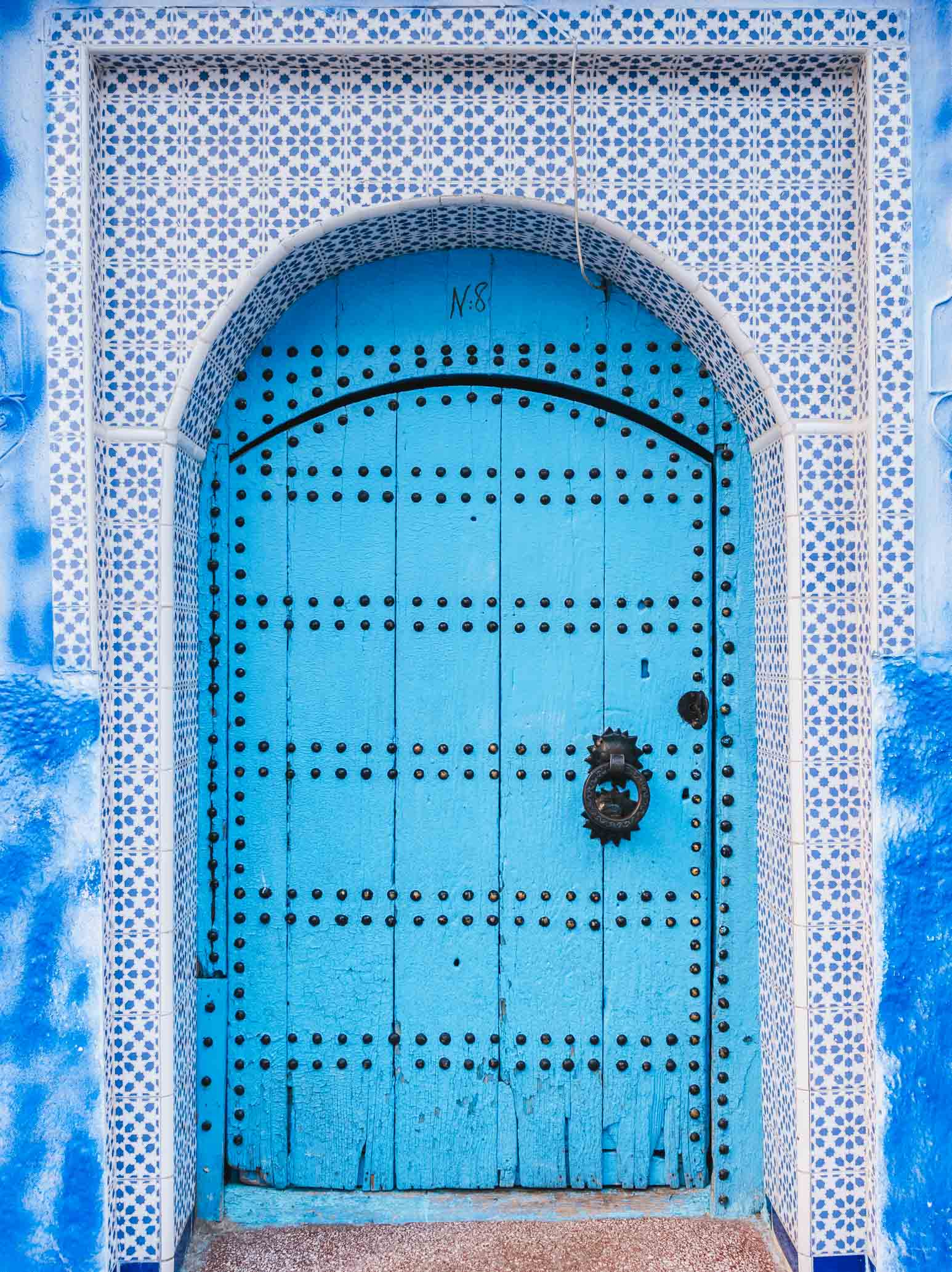 Porte bleue en arche avec clous noir - Nomade Amoureux